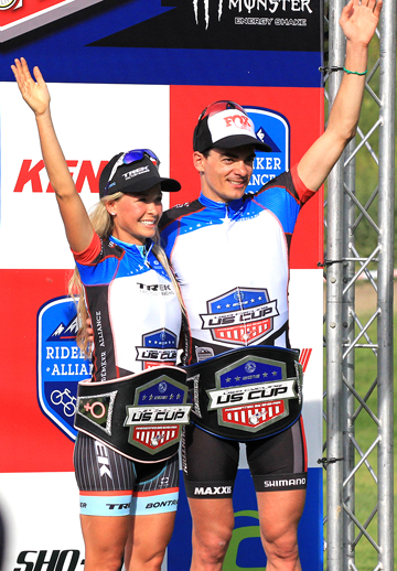 Emily Batty (Trek Factory Racing)  and Raphael Gagne (Rocky Mountain) with their US Cup leaders' belts and jerseys on the podium  ©  Ridebiker Alliance