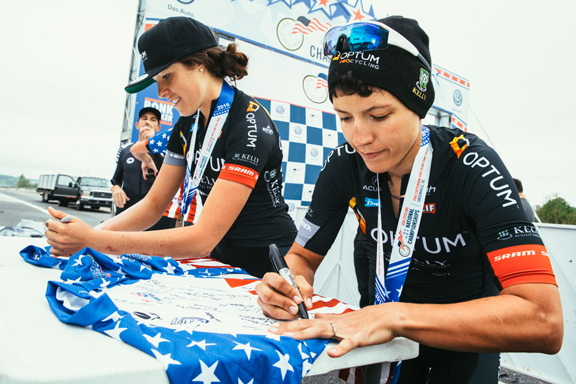 Brianna Walle and Anne Ewart sign souvenir stars and stripes jerseys after receiving their medals. [P] Sam Wiebe