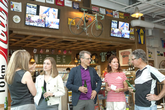 Alex Stieda (Center) and guests enjoy a beer while discussing World Bicycle Relief at the Musette Cafe [P] Heinz Ruckemann